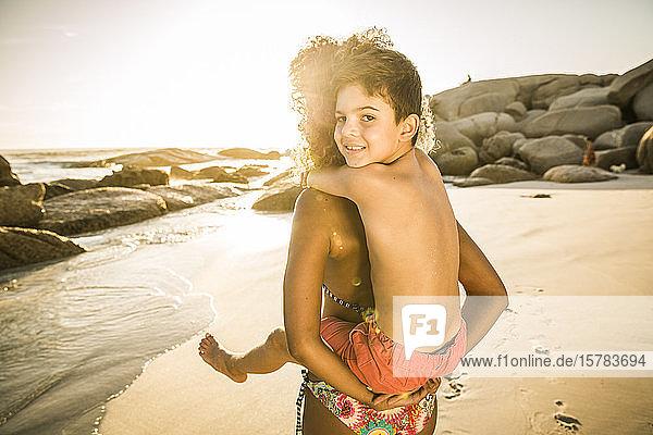Mutter trägt ihren lächelnden Sohn huckepack am Strand