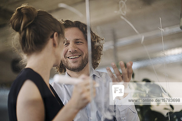 Smiling businessman and businesswoman working on a project in office