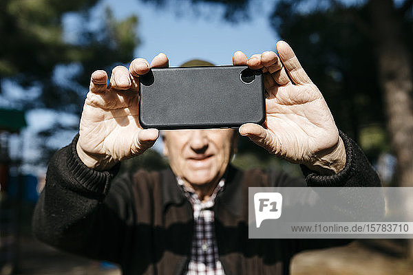 Old man taking pictutes with his smartphone