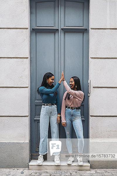 Zwei glückliche junge Frauen  die sich an einer Tür in der Stadt zudröhnen