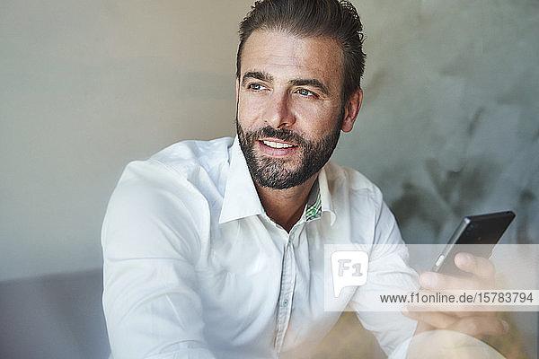 Porträt eines lächelnden Geschäftsmannes mit weißem Hemd und Handy in der Hand