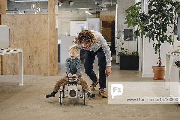 Businessman pushing son on toy car in office