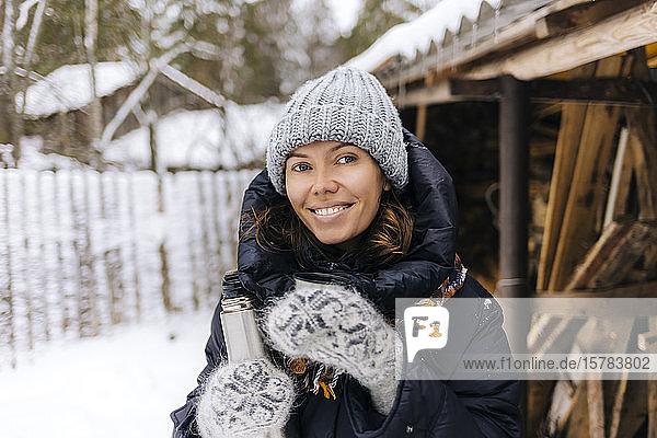 Porträt einer glücklichen Frau mit Thermoskanne im Winter