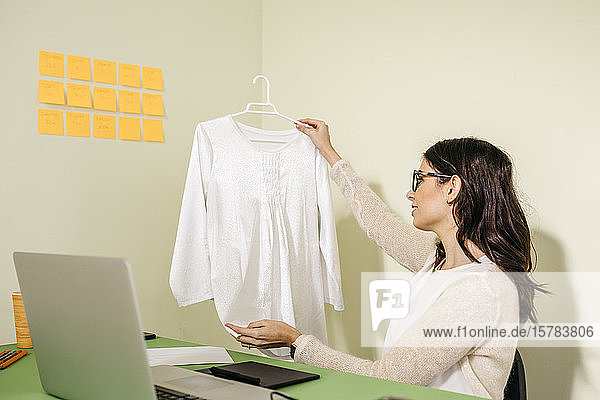 Young woman sitting at desk in office examining garment
