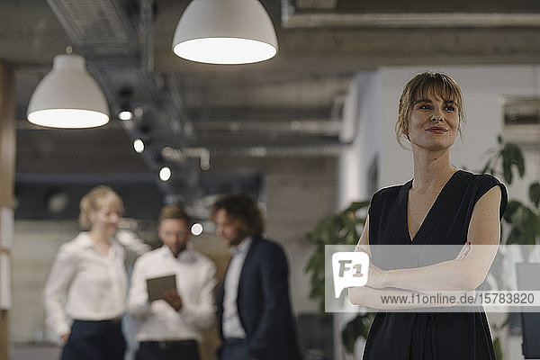 Portrait of confident businesswoman in office with colleagues in background