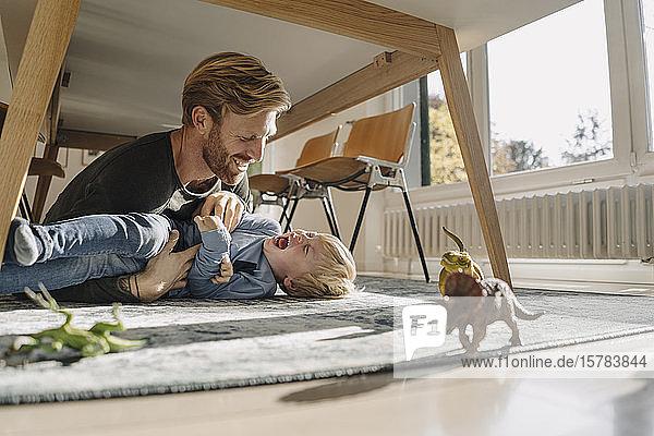 Vater und Sohn spielen zu Hause unter dem Tisch