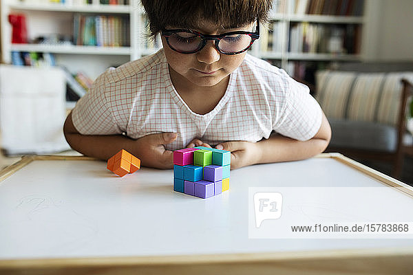 Little boy with glasses playing with building blocks at home