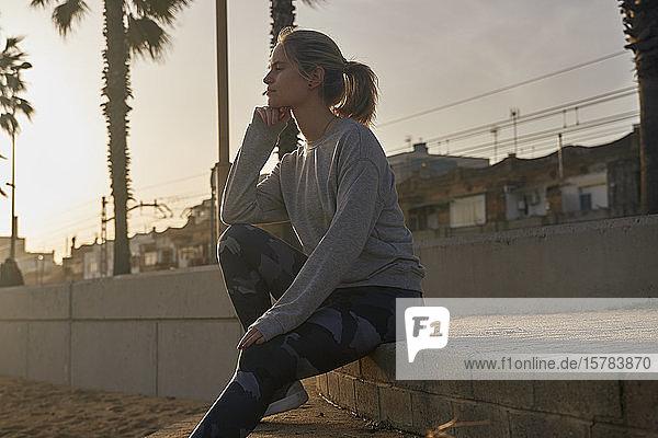 Sportliche junge Frau macht bei Sonnenuntergang eine Pause auf der Strandpromenade
