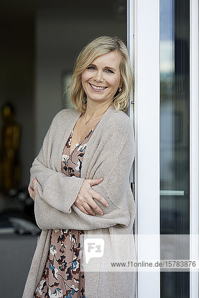 Portait of smiling blond woman leaning against balcony door at home