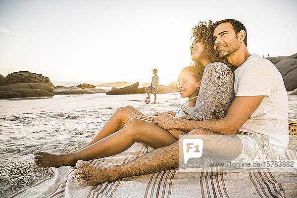 Familie genießt Sonnenuntergang am Strand