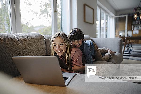 Mutter und Sohn liegen auf dem Sofa und benutzen einen Laptop