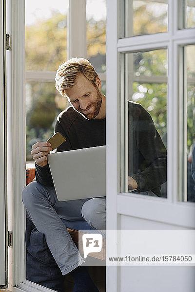 Lächelnder Mann mit Laptop und Kreditkarte im Wintergarten zu Hause