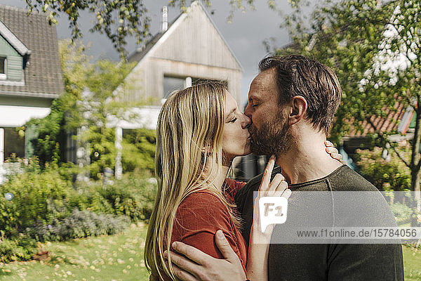 Glückliches Paar küsst sich im Garten  vor ihrem Traumhaus