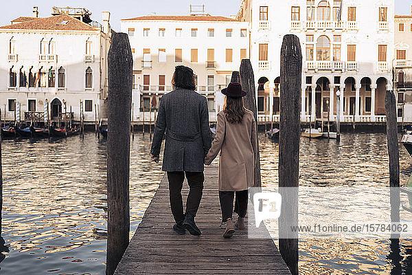 Rückansicht eines jungen Paares beim Spaziergang auf einem Steg am Canal Grande in Venedig  Italien