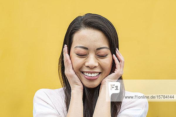 Porträt einer glücklichen Frau mit geschlossenen Augen vor gelbem Hintergrund