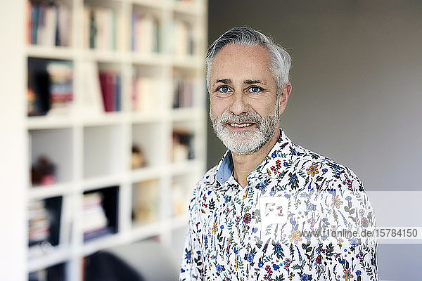 Portrait of mature man wearing patterned shirt at home