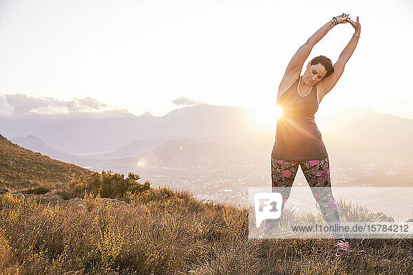 Plus-Size-Model doing sports in the countryside at sunset