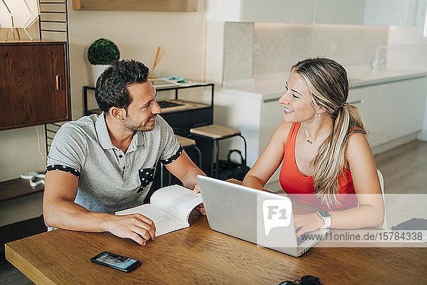 Glückliches Paar sitzt am Tisch mit Laptop und Buch