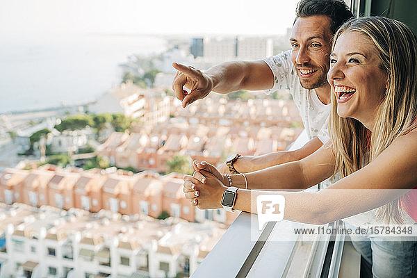 Glückliches Paar schaut in Küstenstadt aus dem Fenster