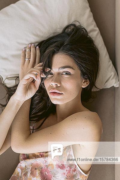 Porträt einer schönen jungen Frau im Bett liegend