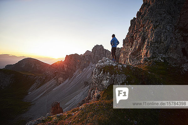 Mountain runner taking a break  watching sunrise at Axamer Lizum  Austria