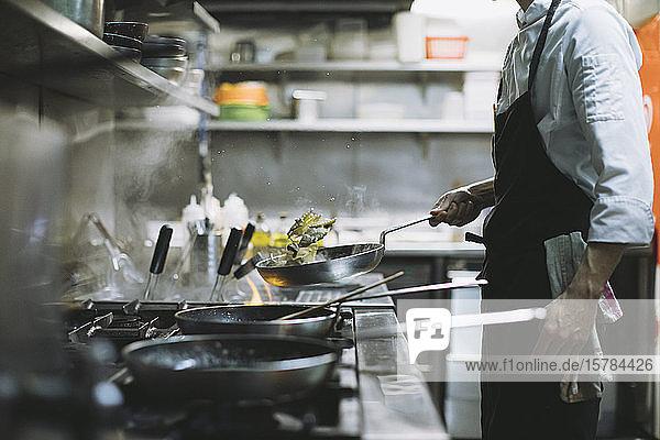 Koch  der ein Gericht am Gasherd in der Restaurantküche zubereitet