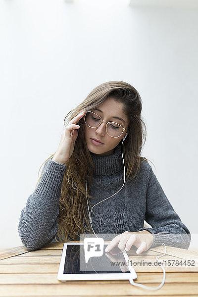 Porträt einer jungen Frau  die an einem Holztisch sitzt und Kopfhörer und digitales Tablett benutzt
