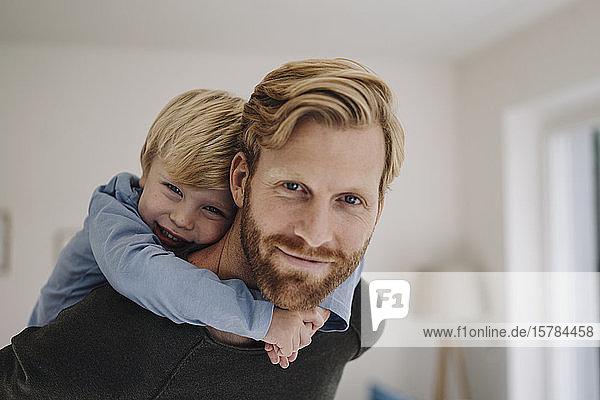 Porträt eines lächelnden Vaters  der seinen Sohn huckepack zu Hause trägt