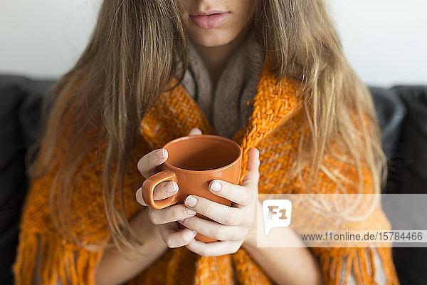 Schrägansicht einer jungen Frau  die auf einer Couch sitzt und einen orangefarbenen Becher hält
