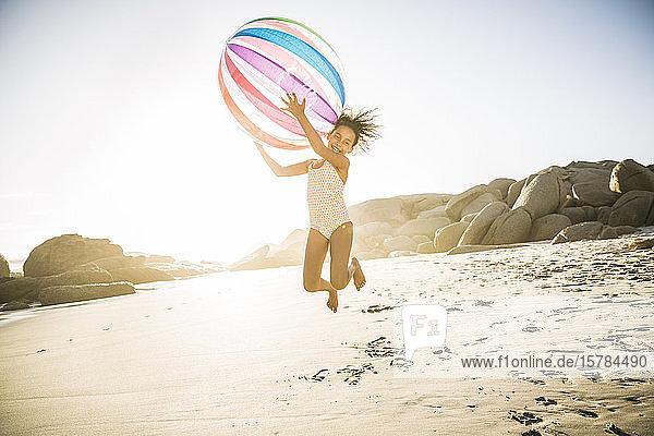 Glückliches Mädchen spielt mit aufblasbarem Ball am Strand