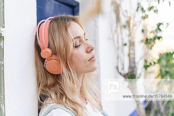 Porträt einer jungen blonden Frau mit geschlossenen Augen  die sich an die Fassade lehnt und mit Kopfhörern Musik hört