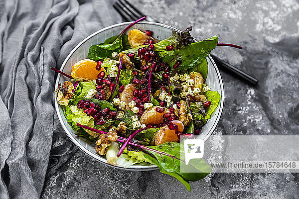 Winter salad with lettuce  tangerines  walnuts  feta and pomegranate seeds