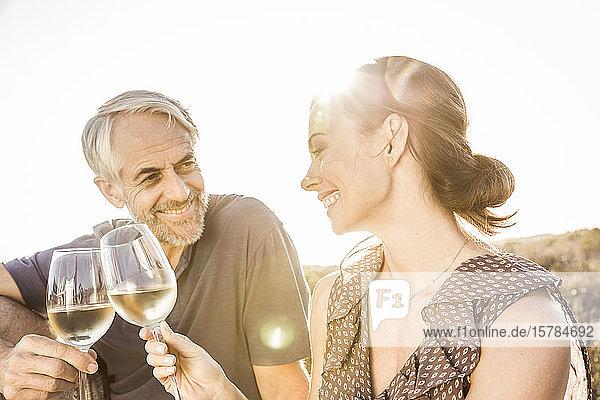 Glückliches Paar trinkt bei Sonnenuntergang ein Glas Weißwein Glückliches Paar trinkt bei Sonnenuntergang ein Glas Weißwein