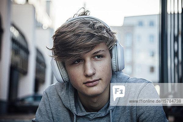 Porträt eines Teenagers mit Kopfhörern  der auf Stufen in der Stadt sitzt