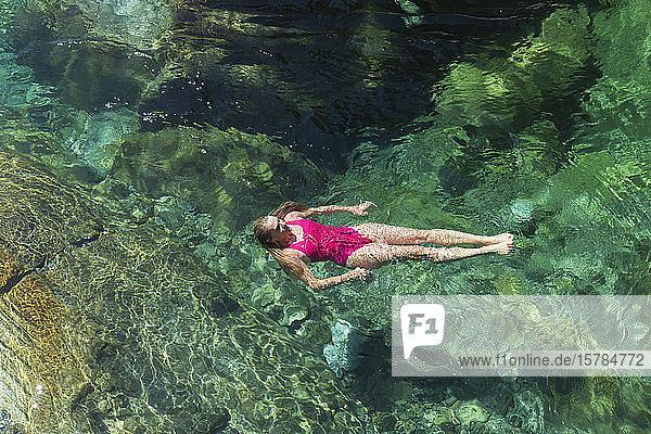 Frau schwimmt im erfrischenden Fluss Verszasca