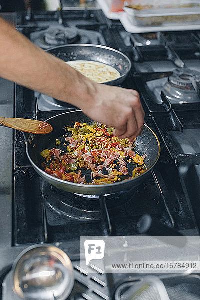 Koch  der ein Gericht in der Restaurantküche zubereitet
