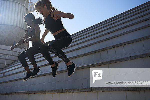 Sportlerinnen  die von einer Treppe springen