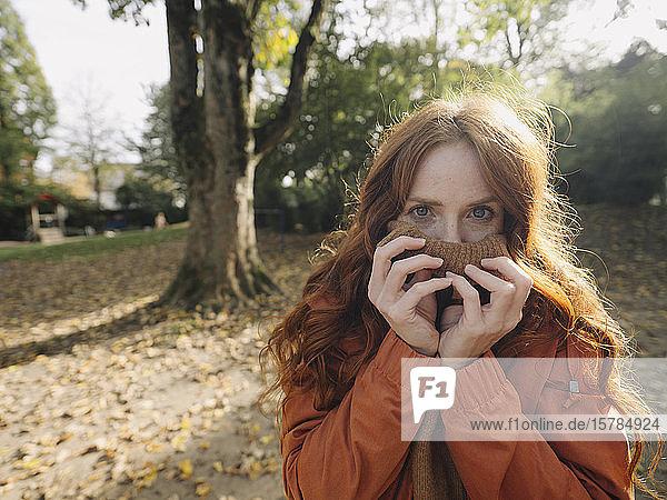 Porträt einer rothaarigen Frau in einem Park im Herbst