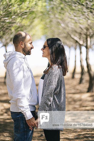 Paar  das sich in einem Park an den Händen hält  von Angesicht zu Angesicht