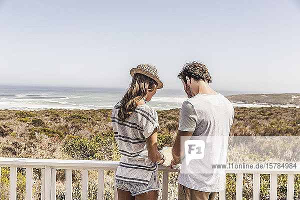 Rear view of young couple standing on a terrace at the sea