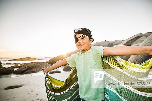 Als Pirat verkleideter Junge am Strand