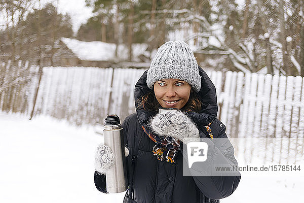 Portrait of smiling woman using thermo flask in winter