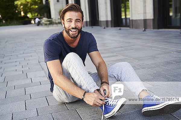Porträt eines glücklichen Mannes  der in der Stadt auf dem Boden sitzt und seine Schuhe schnürt