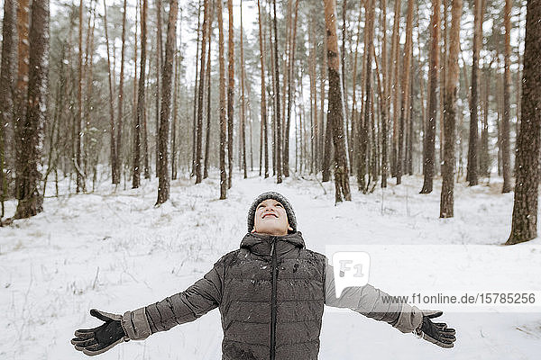 Boy catching snowflakes in winter forest