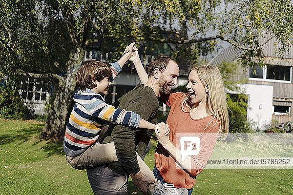 Eltern und Sohn amüsieren sich  spielen im Garten