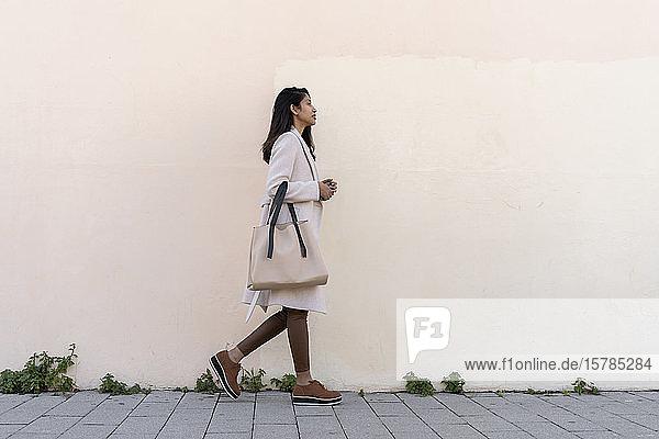 Junge Frau geht an einer Mauer entlang