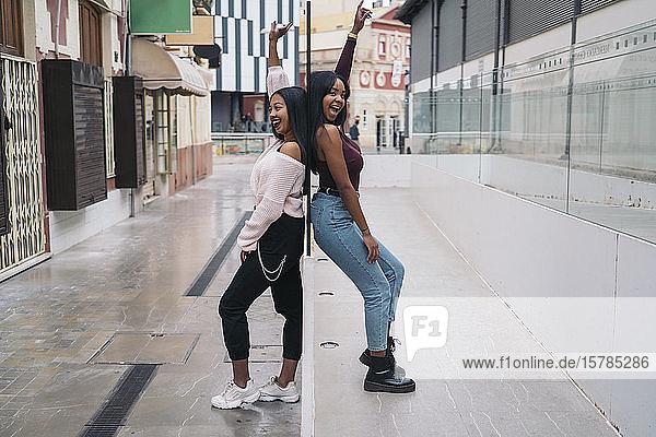 Porträt von zwei glücklichen jungen Frauen  die Rücken an Rücken in der Stadt stehen