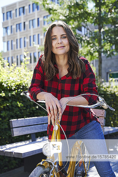 Portrait of brunette woman with bicycle in the city