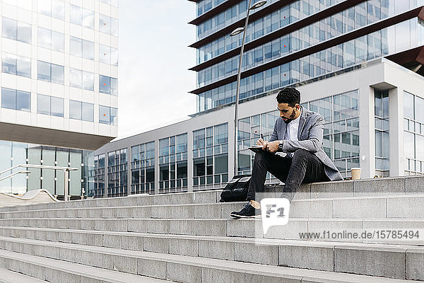 Casual young businessman sitting on stairs in the city taking notes