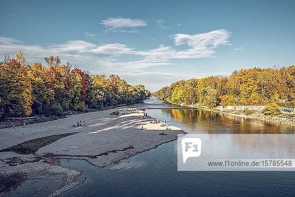 Menschen entspannen sich im Herbst an der Isar im Nordenglischen Garten  Oberfohring  München  Deutschland